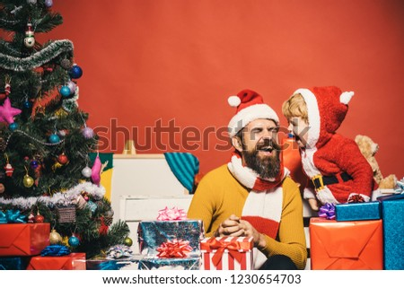 Santa and little assistant among gift boxes by Christmas tree. Christmas family opens presents on dark red background. Winter holiday concept. Man with beard and cheerful face laughs together with son