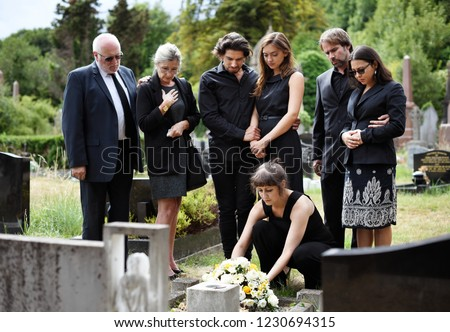 Family laying flowers on the grave #1230694315