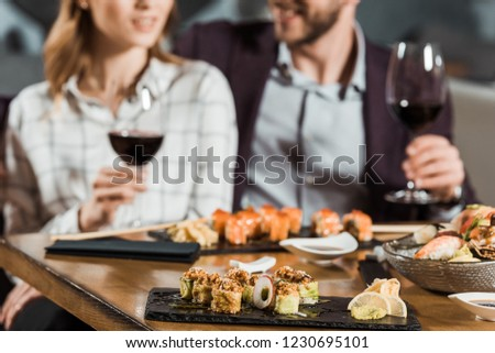 Partial view of couple eating sushi and drinking wine while having date in restaurant #1230695101