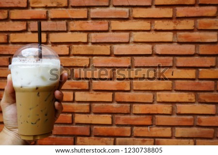Hold a cool coffee cup with red brick background #1230738805
