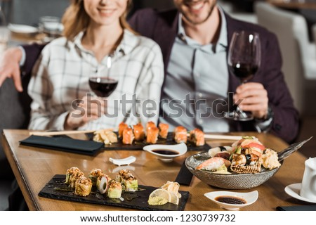 Partial view of smiling couple eating sushi and drinking wine in restaurant #1230739732