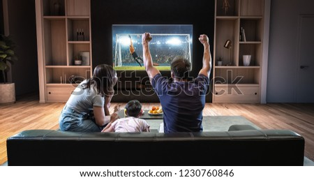 A family is watching a soccer moment on the TV and celebrating a goal, sitting on the couch in the living room. The living room is made in 3D. #1230760846