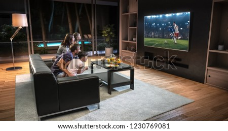 A family is watching a soccer moment on the TV and celebrating a goal, sitting on the couch in the living room. The living room is made in 3D. #1230769081