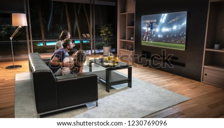 A family is watching a soccer moment on the TV and celebrating a goal, sitting on the couch in the living room. The living room is made in 3D. #1230769096