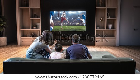 A family is watching a soccer moment on the TV and celebrating a goal, sitting on the couch in the living room. The living room is made in 3D. #1230772165