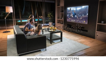 A family is watching a soccer moment on the TV and celebrating a goal, sitting on the couch in the living room. The living room is made in 3D. #1230775996