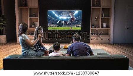 A family is watching a soccer moment on the TV and celebrating a goal, sitting on the couch in the living room. The living room is made in 3D. #1230780847