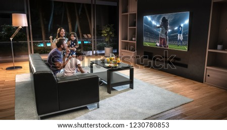 A family is watching a soccer moment on the TV and celebrating a goal, sitting on the couch in the living room. The living room is made in 3D. #1230780853