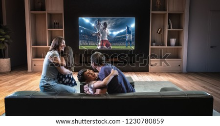 A family is watching a soccer moment on the TV and celebrating a goal, sitting on the couch in the living room. The living room is made in 3D. #1230780859