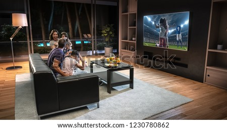 A family is watching a soccer moment on the TV and celebrating a goal, sitting on the couch in the living room. The living room is made in 3D. #1230780862