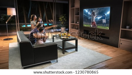 A family is watching a soccer moment on the TV and celebrating a goal, sitting on the couch in the living room. The living room is made in 3D. #1230780865