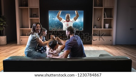 A family is watching a soccer moment on the TV and celebrating a goal, sitting on the couch in the living room. The living room is made in 3D. #1230784867