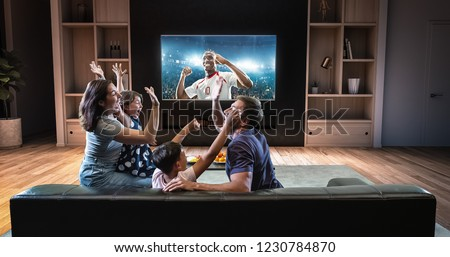 A family is watching a soccer moment on the TV and celebrating a goal, sitting on the couch in the living room. The living room is made in 3D. #1230784870
