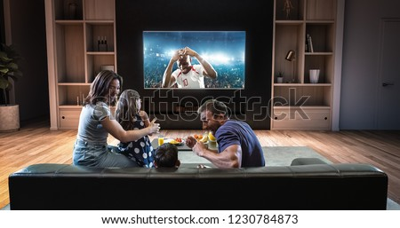 A family is watching a soccer moment on the TV and celebrating a goal, sitting on the couch in the living room. The living room is made in 3D. #1230784873
