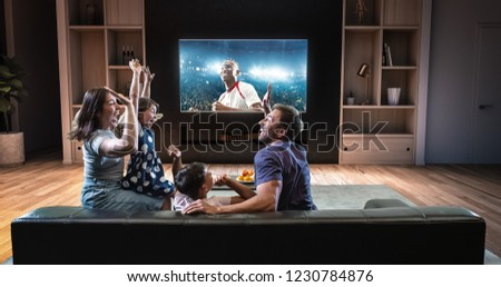 A family is watching a soccer moment on the TV and celebrating a goal, sitting on the couch in the living room. The living room is made in 3D. #1230784876