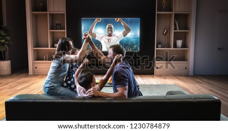 A family is watching a soccer moment on the TV and celebrating a goal, sitting on the couch in the living room. The living room is made in 3D. #1230784879
