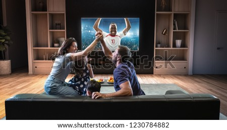 A family is watching a soccer moment on the TV and celebrating a goal, sitting on the couch in the living room. The living room is made in 3D. #1230784882
