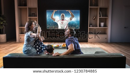 A family is watching a soccer moment on the TV and celebrating a goal, sitting on the couch in the living room. The living room is made in 3D. #1230784885