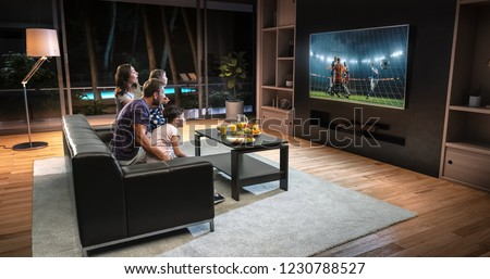 A family is watching a soccer moment on the TV and celebrating a goal, sitting on the couch in the living room. The living room is made in 3D. #1230788527