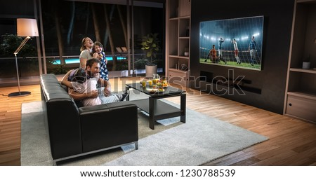 A family is watching a soccer moment on the TV and celebrating a goal, sitting on the couch in the living room. The living room is made in 3D. #1230788539