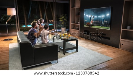 A family is watching a soccer moment on the TV and celebrating a goal, sitting on the couch in the living room. The living room is made in 3D. #1230788542