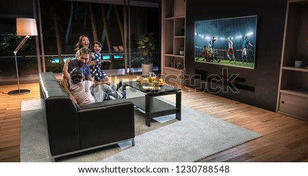 A family is watching a soccer moment on the TV and celebrating a goal, sitting on the couch in the living room. The living room is made in 3D. #1230788548