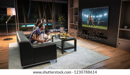A family is watching a soccer moment on the TV and celebrating a goal, sitting on the couch in the living room. The living room is made in 3D. #1230788614