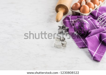 Christmas baking purple gifts decorations eggs and kitchen utensil on marble table. #1230808522