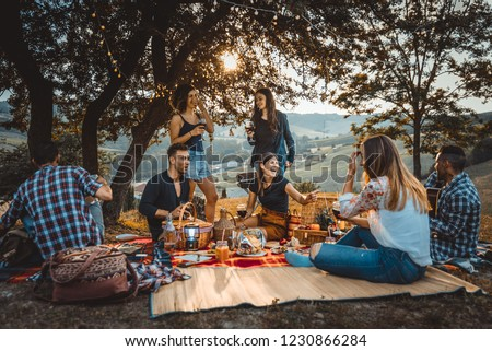 Group of young happy friends having pic-nic outdoors - People having fun and celebrating while grilling ata barbacue party in a countryside #1230866284