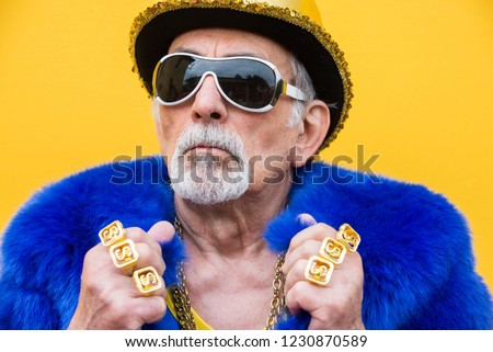 Funny and extravagant senior man posing on colored background - Youthful old man in the sixties having fun and partying Royalty-Free Stock Photo #1230870589