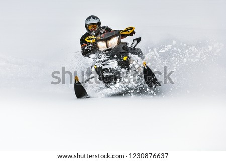 In deep snowdrift snowmobile rider make fast turn. Riding with fun in deep snow powder during backcountry tour. Extreme sport adventure, outdoor activity during winter holiday on ski mountain resort. #1230876637