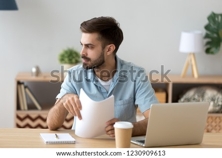 Serious millennial male sit at office table with coffee and laptop distracted from work thinking, thoughtful man holding paperwork documents look in distance planning or considering something #1230909613