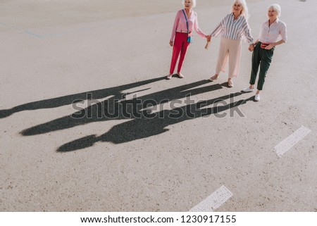 Top view of three beautiful older ladies holding hands each other while standing on the road #1230917155