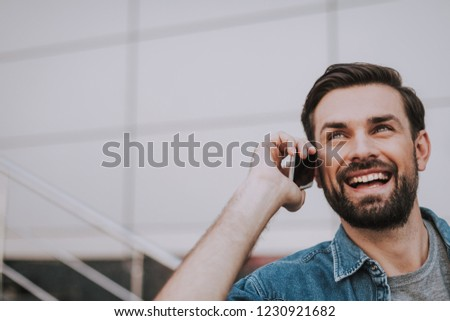 Portrait of cheerful man telling on phone while keeping it in hand. Copy space. Glad guy using appliance during communication concept #1230921682