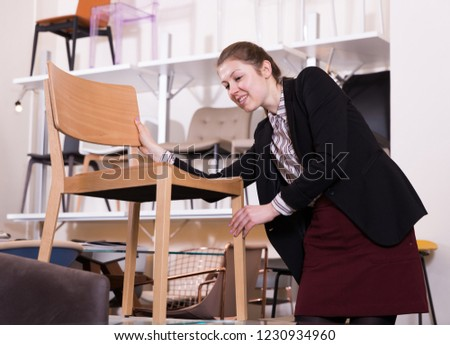 Young woman choosing stylish chairs for apartment in salon of furniture #1230934960