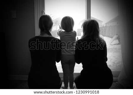 A grandmother, daughter and granddaughter looking out a window. #1230991018