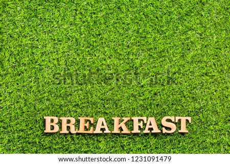 Word breakfast in wooden letters - Green grass. Background for design #1231091479