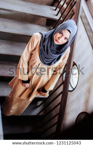 Portrait of a young  beautiful Muslim Arabic woman in a brown head scarf turban. She is elegantly dressed in conservative but modern and minimalist clothing which is fashionable. #1231125043