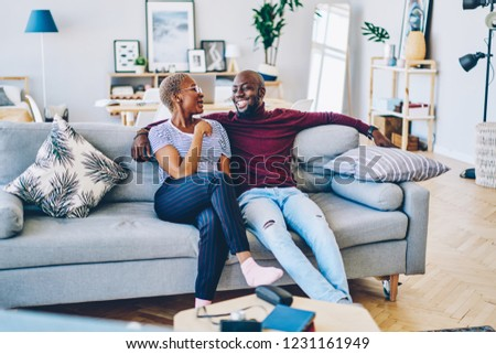 African american couple in love having conversation sitting at sofa at apartment,positive young marriage talking to each other recalling funny stories during free time in comfortable living room #1231161949