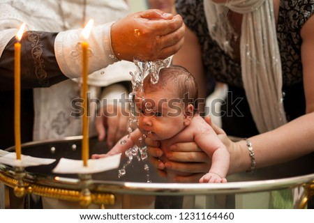 Newborn baby baptism in Holy water. baby holding mother's hands. Infant bathe in water. Baptism in the font. Sacrament of baptism. Child and God. Christening candle Holy water font. The priest baptize #1231164460