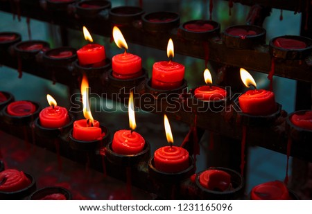 Red candles with yellow flame on catholic church altar. Burning candle closeup photo. In memoriam banner template. Christian church altar closeup. Religious cult belief. Pray candles flaming in dark