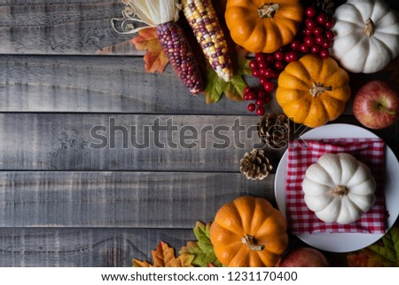 Top view of  Autumn maple leaves with Pumpkin, apple, corn and red berries on old wooden background. Thanksgiving day concept. #1231170400