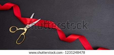 Grand opening. Top view of gold scissors cutting red silk ribbon against black background, banner, copy space. #1231248478