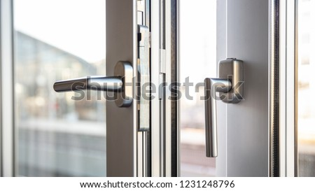 Close up view of aluminum door window handles, against a blurry background Royalty-Free Stock Photo #1231248796