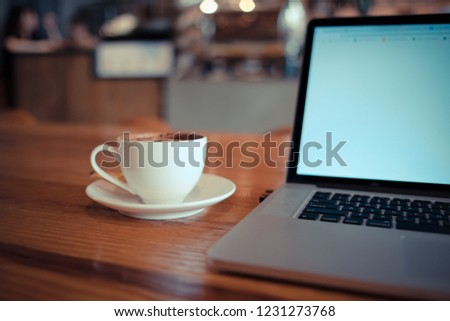A cup of cappuccino coffee or chocolate cacao in a white cup with laptop on table. Royalty high quality free stock photo of drink capuccino or latte coffe with laptop for working in office