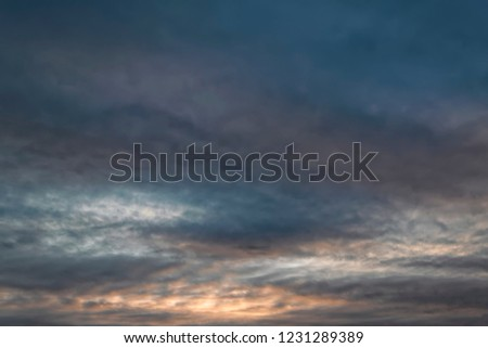 feathery clouds in the blue sky are illuminated by the rays of the sun, setting over the horizon #1231289389