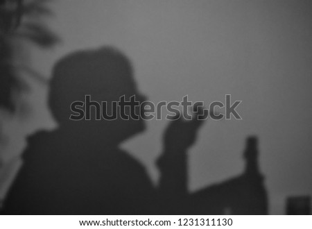 A blurry shadow on the wall of a person smoking a cigarette and holding a wine bottle #1231311130