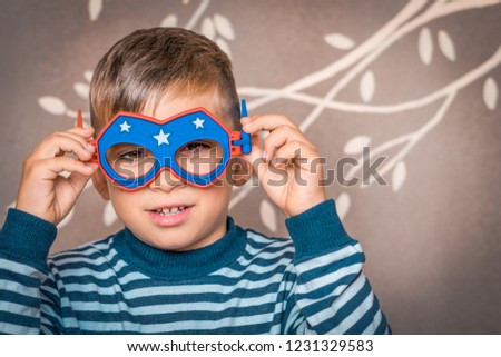 Close portrait of a boy in a striped t-shirt and toy glasses. Kid measures the mask with asterisks. #1231329583