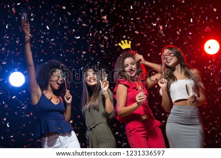 New Year party, women dancing with champagne and photo props at nightclub, copy space #1231336597