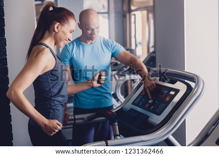 Personal training with a trainer on a treadmill. The trainer controls the correctness of the exercise when using a treadmill for cardio. Control coach in the gym. Athletic jogging with a trainer #1231362466